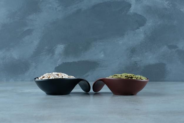 青い背景の上のカップの緑のカボチャとヒマワリの種。高品質の写真