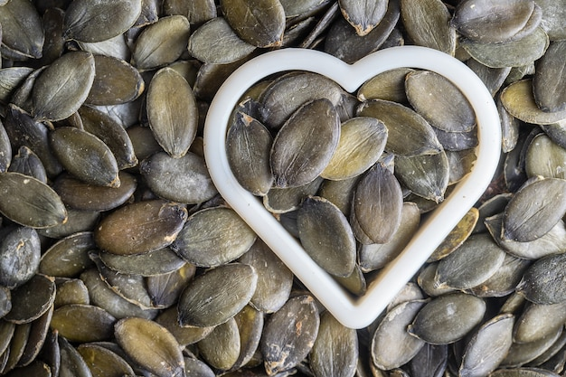 Green pumpkin seeds together with a heart shape as pattern background, close up, top view