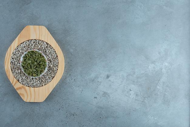 Zucca verde e semi di girasole in tazze su sfondo blu. foto di alta qualità