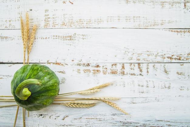 Green pumpkin on wooden table