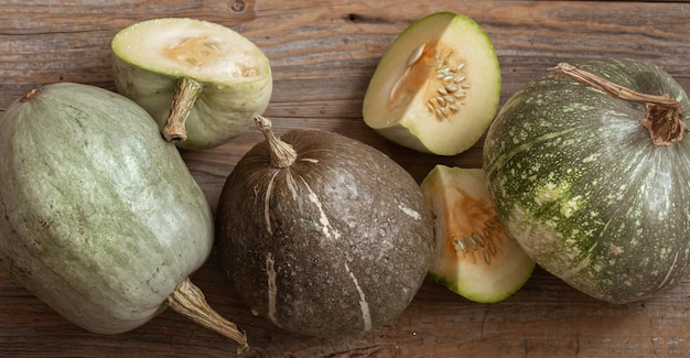 Green pumpkins on a background of wooden boards top view close up. autumn harvest concept.