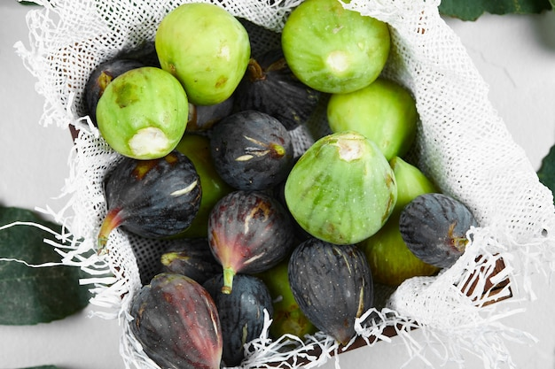 Green and purple figs in a tray on a piece of burlap.