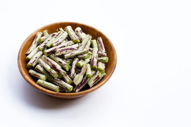 白の木製ボウルに緑紫の庭の長い豆。