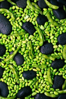 Green raw edamame soybeans and pods on black stone surface. flat lay