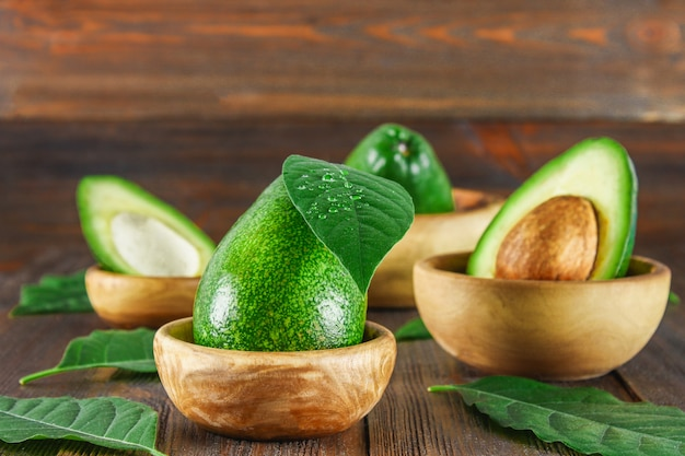 Green raw ripe cut and whole avocado fruits with stone lie in wooden bowls