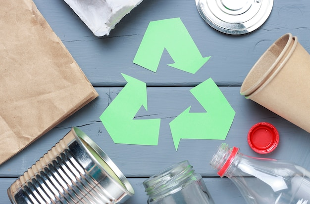 A green recycle garbage symbol and plastic, iron garbage on a gray