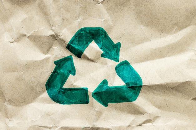 紙の段ボールの背景に緑のリサイクルシンボル、環境にやさしいと持続可能性の概念