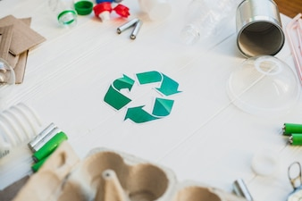 Green recycle symbol surrounded with waste items