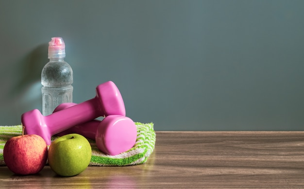 Green and red apples, dumbbells and bottle of water on wood floor with copy space.