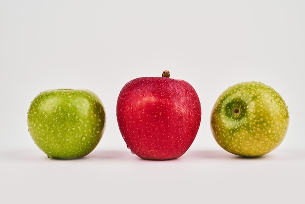 Green and red apples on white surface.