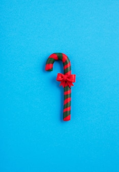 Green and red candy cane with a bow in the blue background, christmas mood