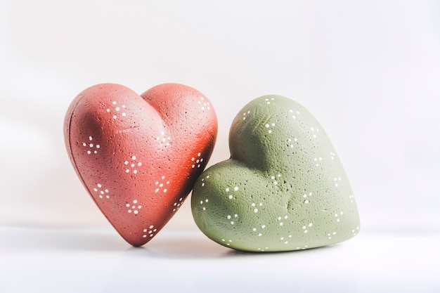 Green and red christmas hearts on white background
