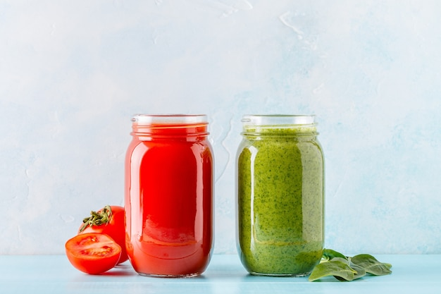 Green/red colored smoothies / juice in a jar on a blue.