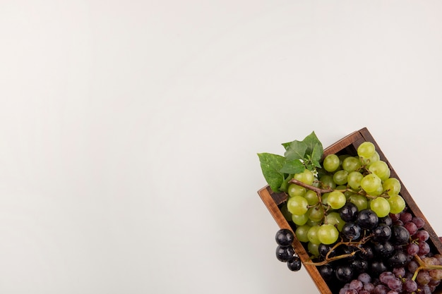 Grappoli d'uva verdi e rossi in una scatola di legno nell'angolo