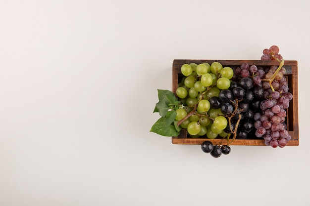 Green and red grape bunches in a wooden box isolated oin white
