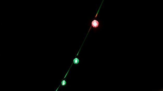 Green and red light bulb decoration on black backdrop