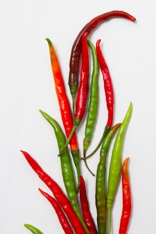 Green and red peppers on plain background