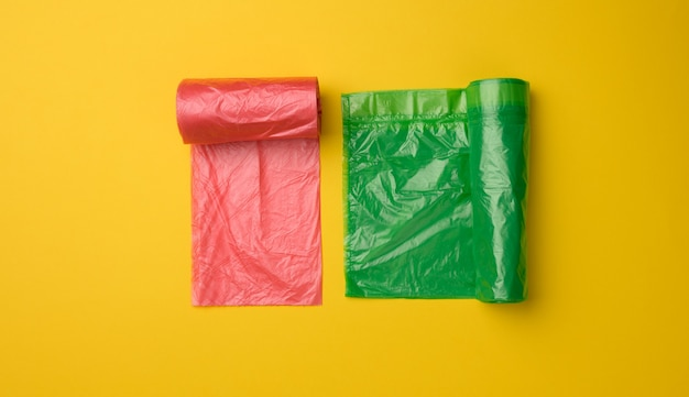 Green and red plastic bags for trash can on yellow background, top view