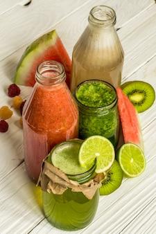 Frullati verdi e rossi in un barattolo con lime, kiwi