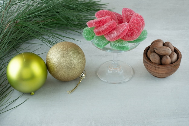 Green and red sugar marmalade with christmas balls on white background. high quality photo