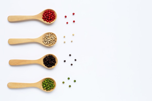 Green, red, white and black peppercorns with wooden spoon on white