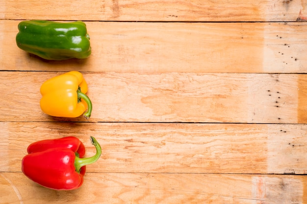 Green; red and yellow bell peppers on wooden plank