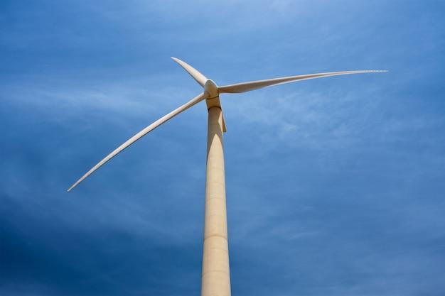 Концепция зеленой возобновляемой альтернативной энергии - турбина ветрогенератора, вырабатывающая электричество в голубом небе