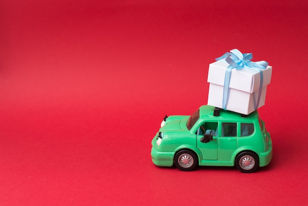 Green retro toy car delivering white gift on red  with copycopyspace