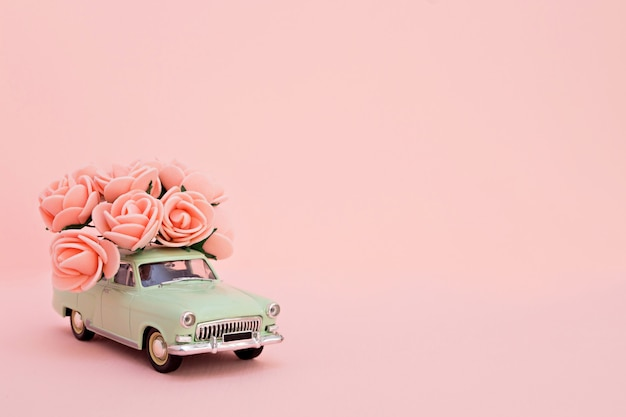 Green retro toy car with a bouquet of flowers on a pink background