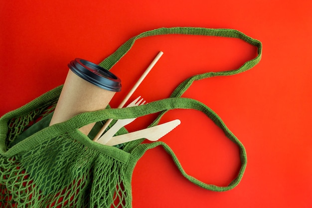 Green reusable shopping string bag with paper cups, straws on red background. zero waste, plastic free items, stop plastic. top view, overhead, template, mockup.