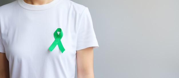 Green ribbon for liver, gallbladders, bile duct, cervical, kidney cancer and lymphoma awareness month. healthcare and world cancer day concept