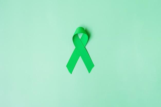 Зеленая лента на фоне зеленого цвета для поддержки людей, живущих и больных. концепция месяца осведомленности рака и донорства органов печени, желчного пузыря, желчного протока