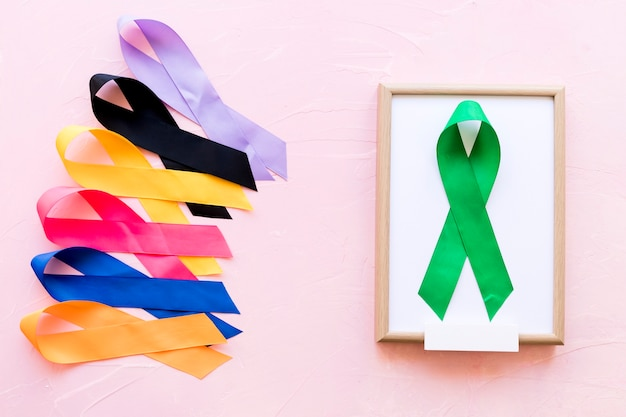 Green ribbon on white wooden frame near the row of colorful awareness ribbon