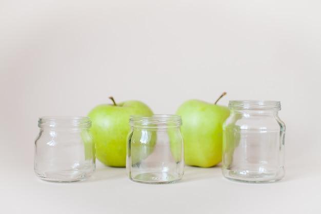 緑の熟したリンゴと灰色の離乳食用の空の透明な瓶。