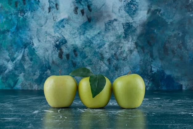 Зеленые спелые яблоки на мраморном столе.