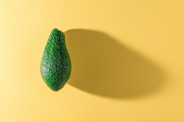 Green ripe avocado on a yellow background. delicious tropical vegetable. flat lay.