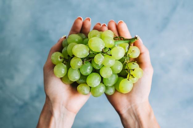 青い背景、クローズアップの手に緑の熟したブドウ。