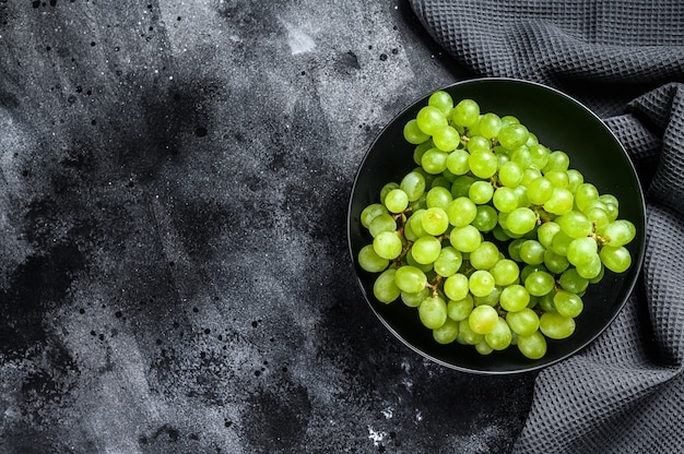 プレート、秋の果物の緑の熟したブドウ。黒の背景