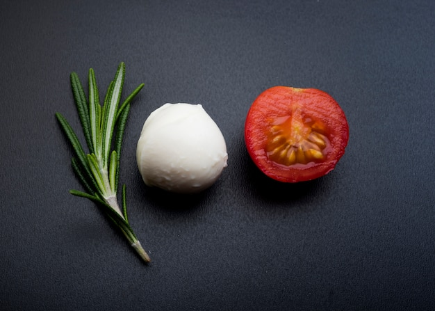 Green rosemary; half cheery tomato and mozzarella cheese over black surface