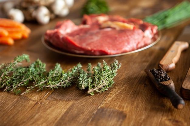 Зеленый розмарин перед двумя кусками красного мяса рядом со свежими овощами и ножом шеф-повара. зеленые травы. вкусное мясо.