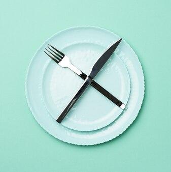 Зеленая круглая керамическая тарелка и скрещенные нож и вилка на зеленом фоне, вид сверху