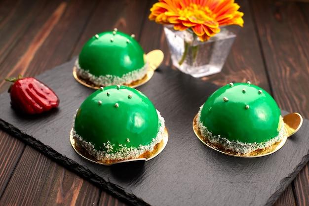 Green round dessert - a cake, on a dark background