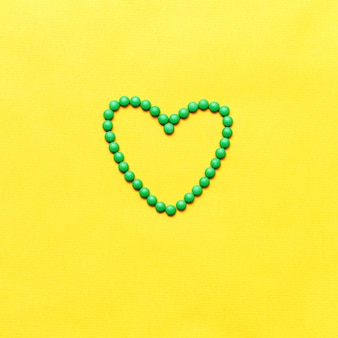 Green round pills tablets heart shape on yuellow background