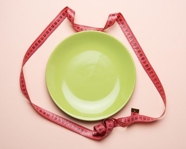 Зеленая круглая тарелка и красная измерительная лента на бежевом фоне, концепция потери веса, плоская планировка