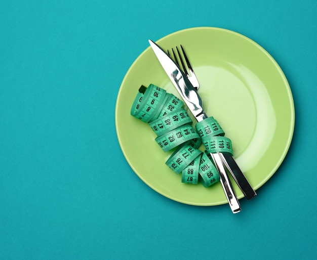 Green round plate and fork and knife wrapped in green measuring tape on blue background, weight loss concept, flat lay