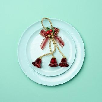 Зеленая круглая красная керамическая тарелка, праздничная сервировка стола на рождество и новый год
