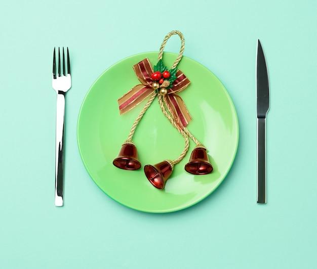 Зеленая круглая красная керамическая тарелка, нож и вилка на зеленом фоне, праздничная сервировка стола на рождество и новый год, вид сверху