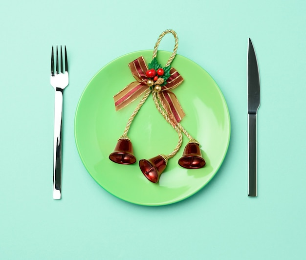 Green round red ceramic plate, knife and fork on green background, festive table setting for christmas and new year, top view