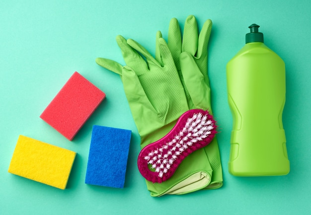 Green rubber gloves for cleaning, multi-colored sponges, brushes and cleaning fluid