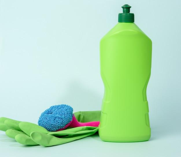 Зеленые резиновые перчатки для очистки и очищающей жидкости в пластиковой бутылке на синем фоне, крупным планом